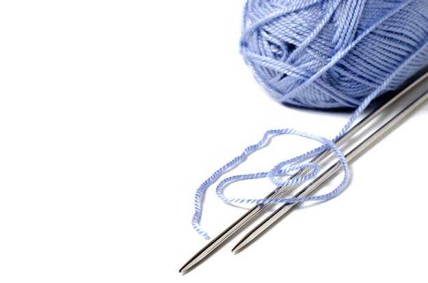 Bolas de hilo azul y agujas de tejer