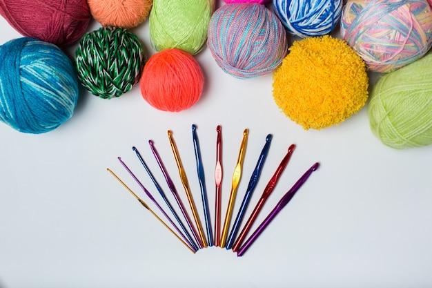 Bolas de hilo de colores del arco iris muestra crochet y agujas de tejer