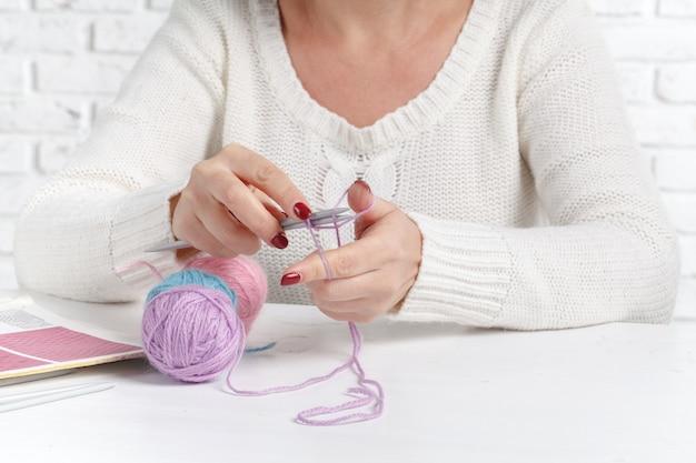 Bolas de hilo de colores. muestra de punto. las manos de las mujeres están tejidas