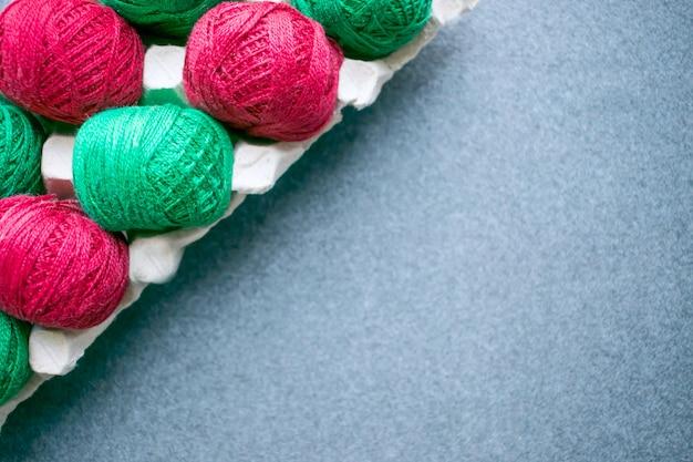Bolas de hilo de colores rojo y verde en una bandeja de huevos de papel
