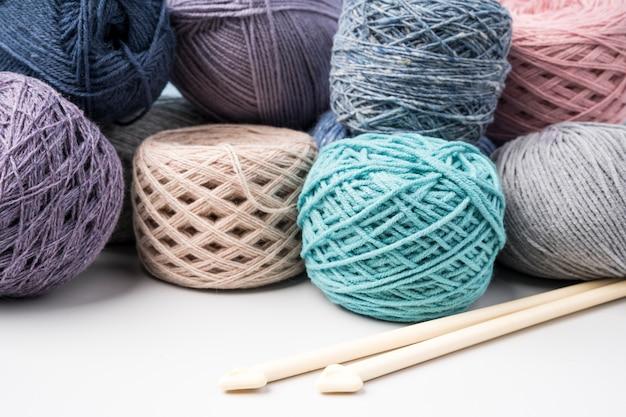 Bolas de hilo de lana de colores en mesa blanca
