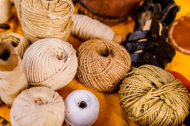 Bolas de hilo, lana y cuerda de colores tierra.