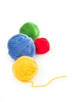 Bolas de hilos de lana azul, rojo y amarillo sobre el fondo blanco.