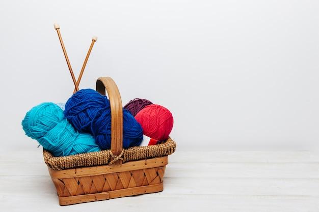 Bolas de lana azules y rojos en cesta