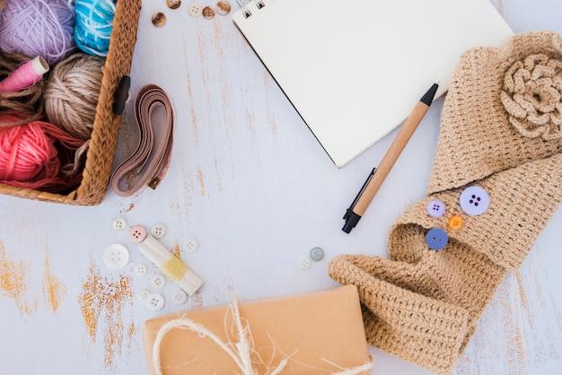 Bolas de lana en la cesta; cinta métrica; botón y ganchillo en escritorio de madera.