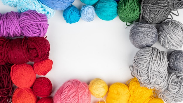 Las bolas de lana para tejer se encuentran sobre una superficie blanca. vista superior. copie el espacio.