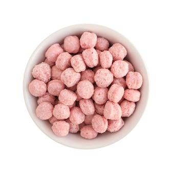 Bolas de maíz rosa de fruta dulce snack en tazón redondo aislado vista superior. t