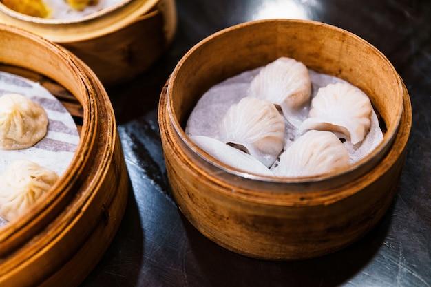 Bolas de masa hervida de camarones chinos (har gow) en la cesta de bambú. servido en un restaurante en taipei, taiwán.