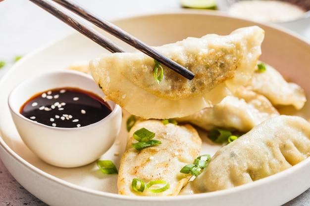 Bolas de masa hervida coreanas fritas con cebolla verde y salsa en un plato blanco.