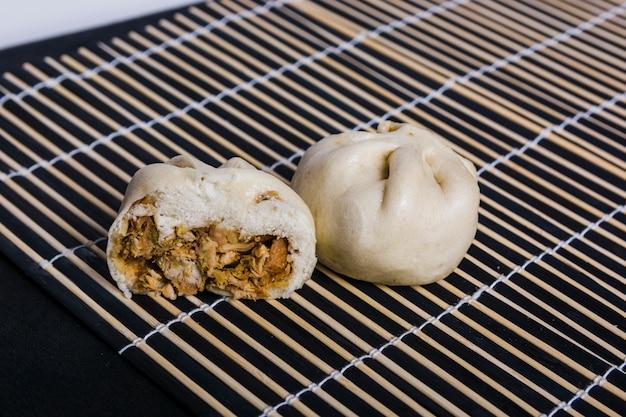 Bolas de masa hervida japonesas con carne de cerdo en mantel individual sobre fondo negro