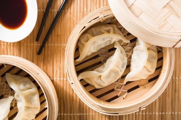 Bolas de masa hervida o gyoza servidas en vapor tradicional y salsa de soja sobre estera de bambú