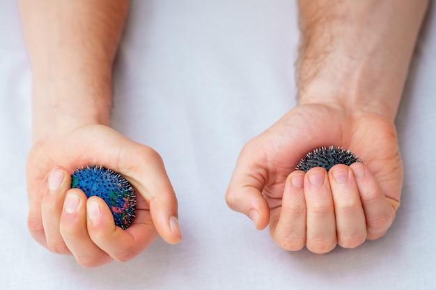 Bolas de masaje de goma en las manos.