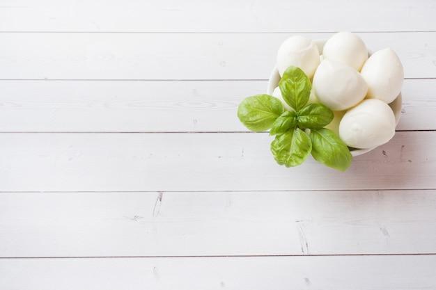 Bolas de mozzarella y albahaca en el plato, enfoque selectivo copiar espacio