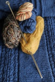 Bolas multicolores de hilo con agujas de tejer en el fondo de una cosa tejida.