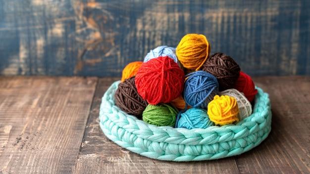 Bolas multicolores de hilo en y cerca del sofá de punto