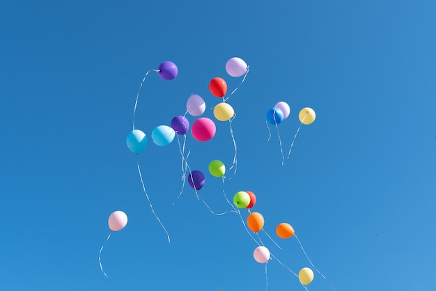 Bolas multicolores lanzadas al cielo azul