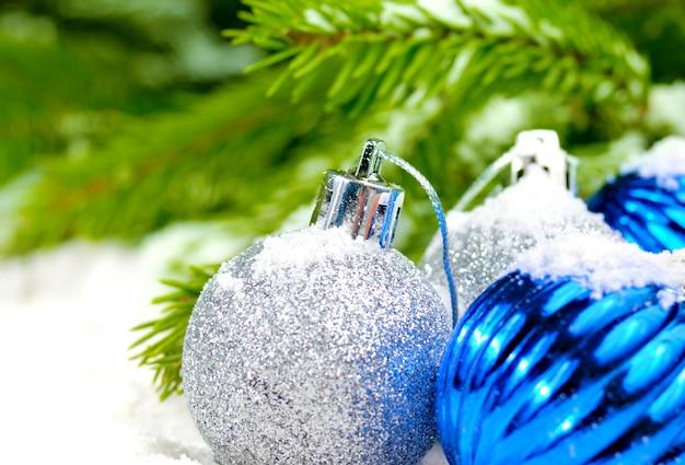 Bolas de navidad azules y plateadas en la nieve cerca de la rama de pino