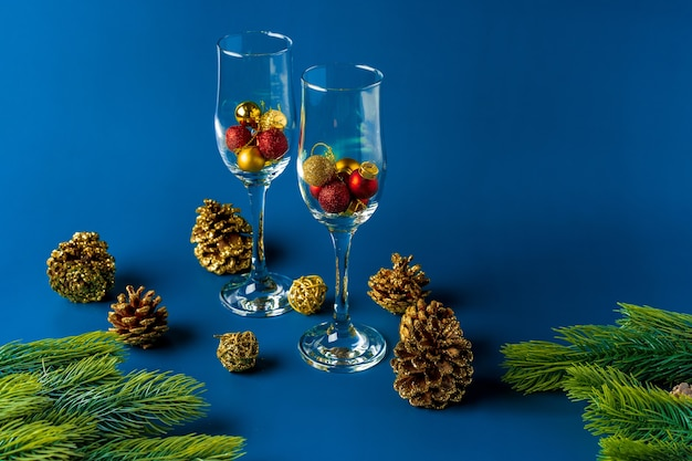 Bolas de navidad en copas de champán vacías concepto de año nuevo en el fondo