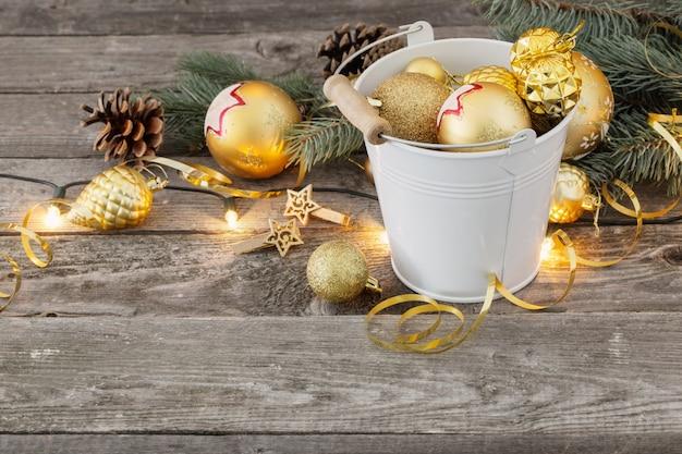 Bolas de navidad doradas en balde sobre madera