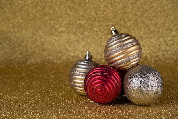 Bolas de navidad doradas y rojas sobre un fondo dorado de brillo