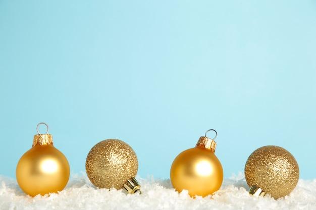 Bolas de navidad doradas sobre la nieve. endecha plana. año nuevo 2022. vista superior