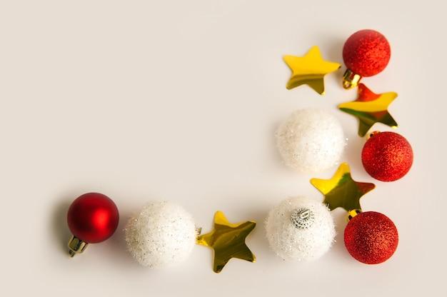 Bolas de navidad y estrellas de confeti doradas sobre un fondo blanco.