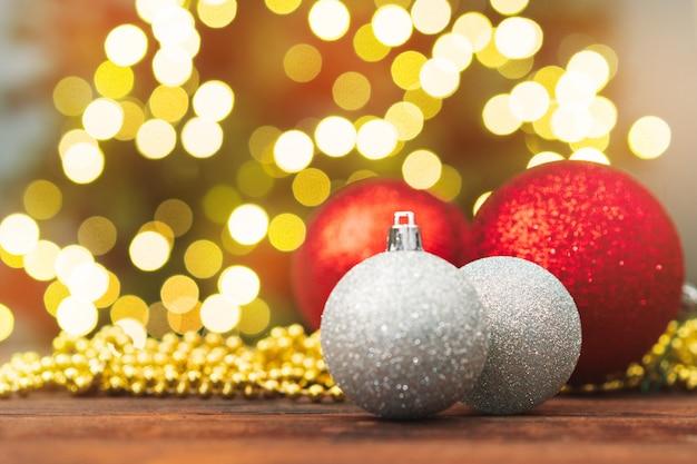Bolas de navidad en una mesa de madera contra el fondo bokeh borrosa brillante