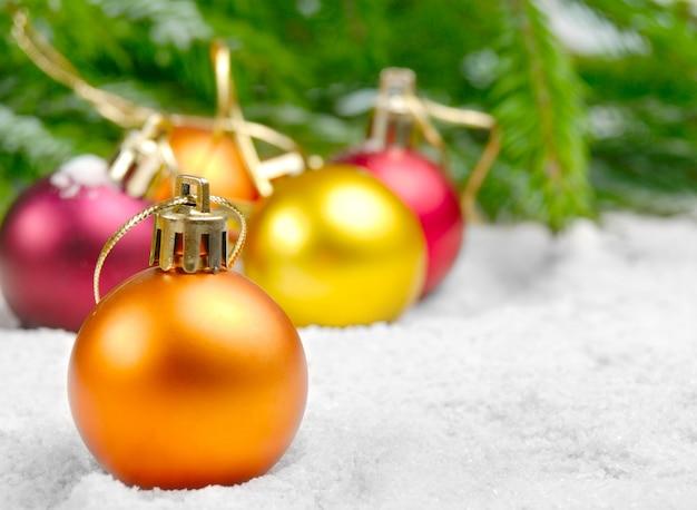 Bolas de navidad en la nieve bajo el pino