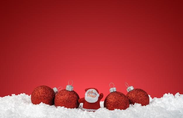Bolas de navidad en la nieve sobre rojo.