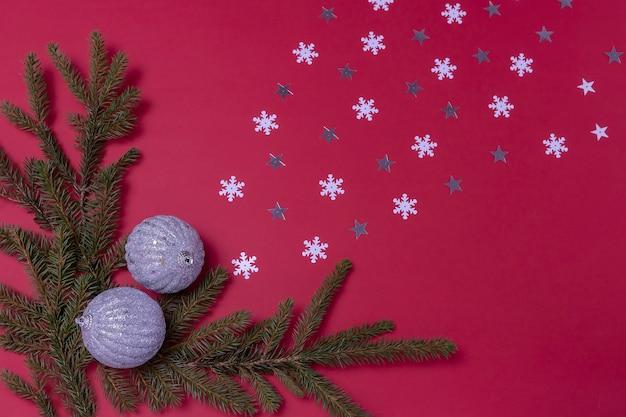 Bolas de navidad ramas de abeto y confeti en forma de copos de nieve y estrellas