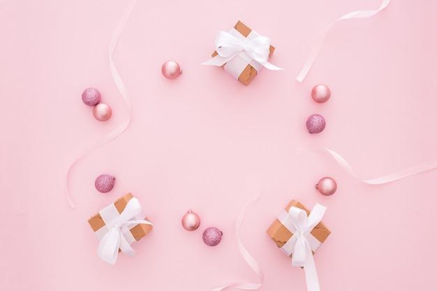 Bolas de navidad y regalos sobre un fondo rosa