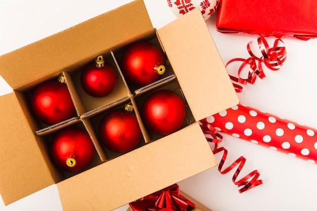 Bolas de navidad rojas en caja marrón