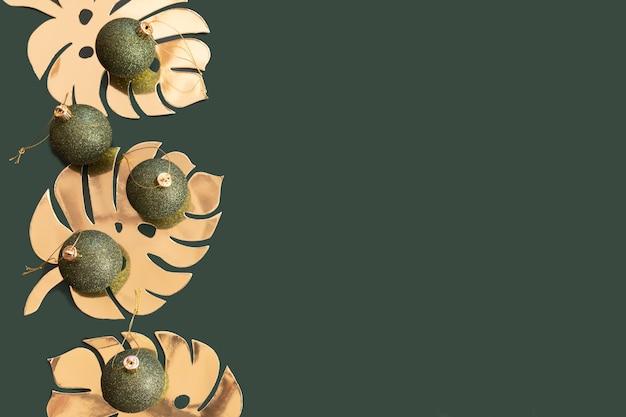 Bolas de navidad verde botella oscura con hojas de monstera de oro sobre un fondo verde azulado