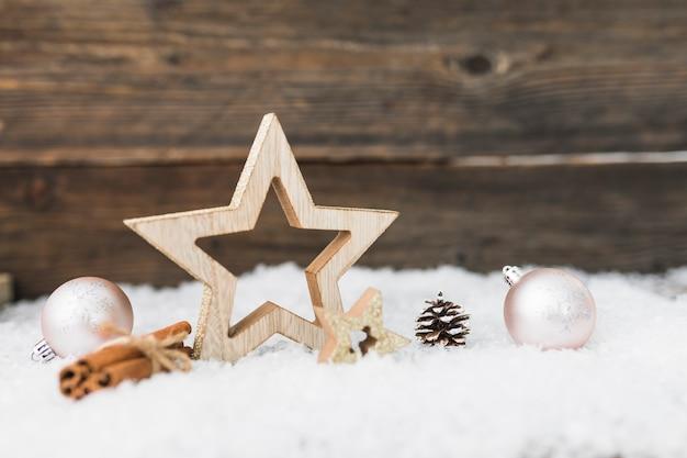 Bolas navideñas cerca de artículos de madera sobre nieve.