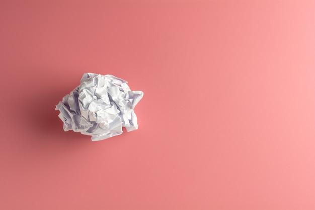Bolas de papel arrugadas en un fondo rosado. para crear su negocio o banner de fondo creativo.