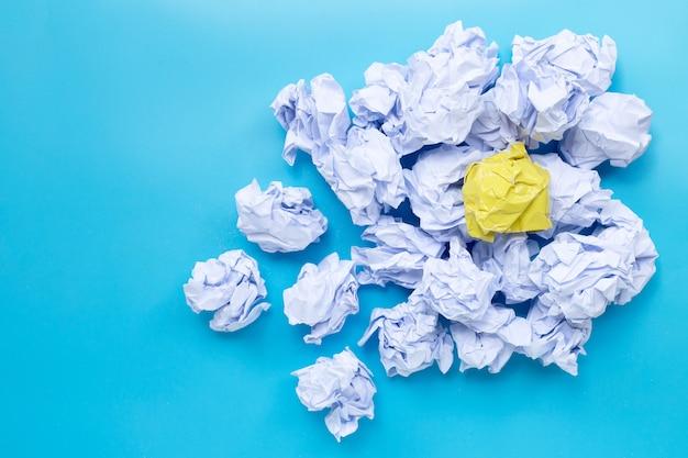 Bolas de papel arrugado blanco y amarillo sobre un fondo azul. vista superior