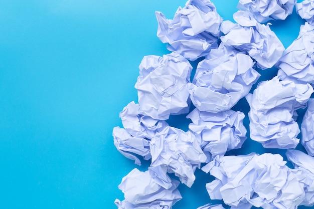 Bolas de papel arrugado blanco sobre un fondo azul.
