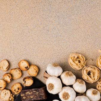Bolas de pasta crudas; bulbos de ajo; rebanadas de pan y queso marrón dispuestos en el fondo del papel tapiz