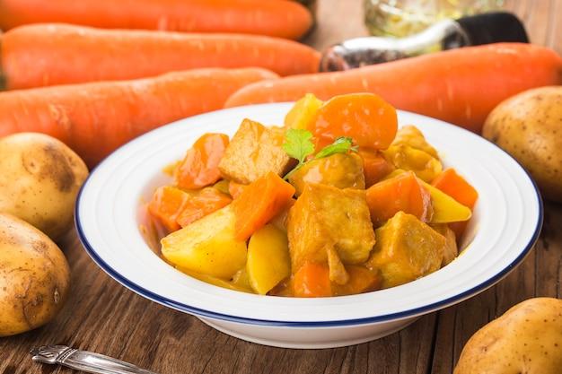 Bolas de pescado con curry, papas y zanahorias