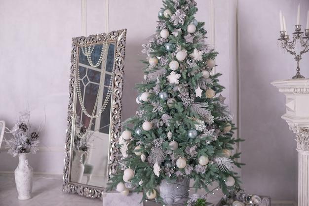 Bolas plateadas y blancas. árbol de navidad con regalos en el interior de lujo. año nuevo en casa interior de navidad con gran espejo y decoración navideña, adornos. sala de vacaciones de invierno