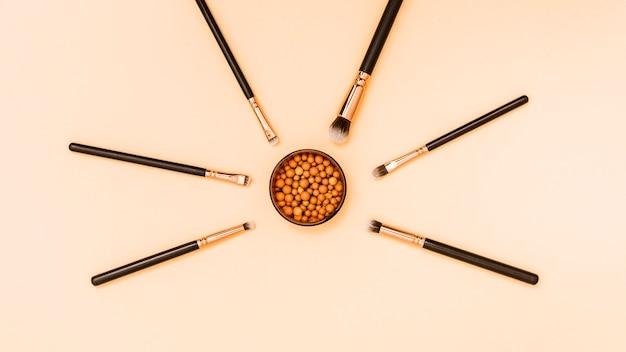 Bolas de polvo facial de maquillaje rodeadas con pinceles de maquillaje sobre fondo beige