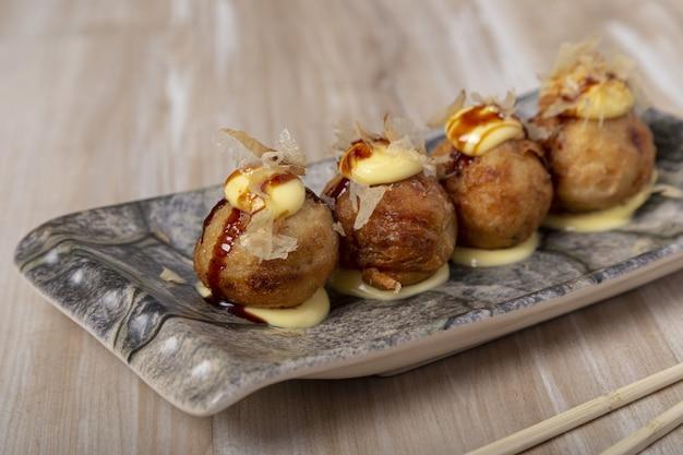 Bolas de pulpo takoyaki de comida japonesa sobre fondo de madera
