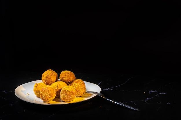 Bolas de queso con ajo y eneldo en su interior para un aperitivo en un plato sobre un fondo negro.