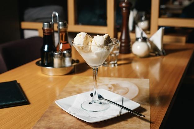 Bolas de relleno de helado en una copa de martini y licor cointreau, sobre una mesa en un restaurante.