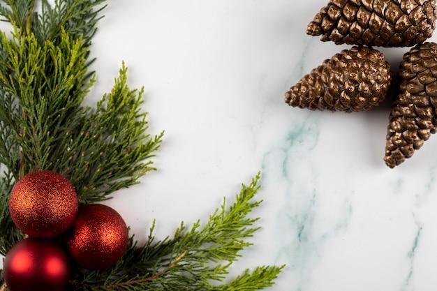 Bolas rojas del árbol de navidad en una rama verde y conos dorados en las esquinas opuestas.