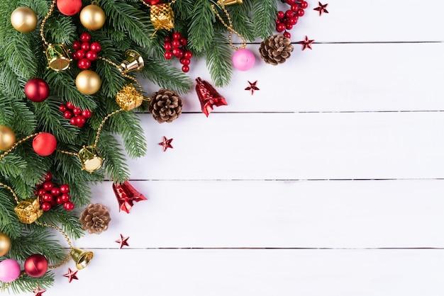 Bolas rojas de la caja de regalo de la navidad con las ramas spruce, los conos del pino, las bayas rojas en el backg de madera