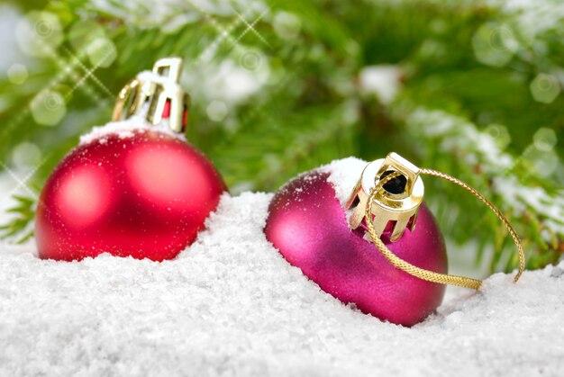 Bolas rojas de navidad en la nieve debajo de la ramita de pino