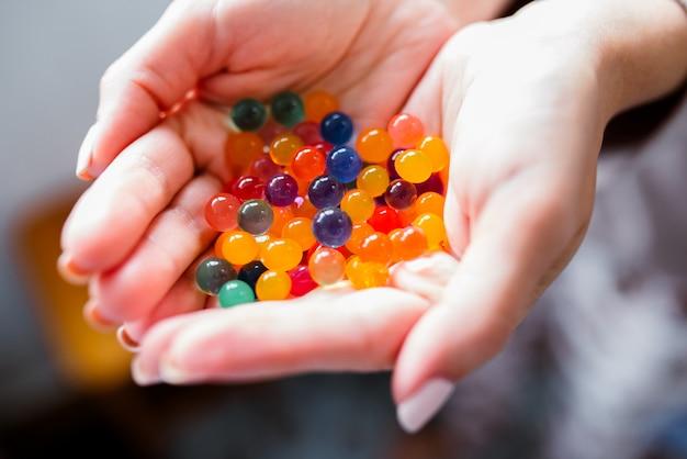 Bolas de vidrio multicolor en sus manos.