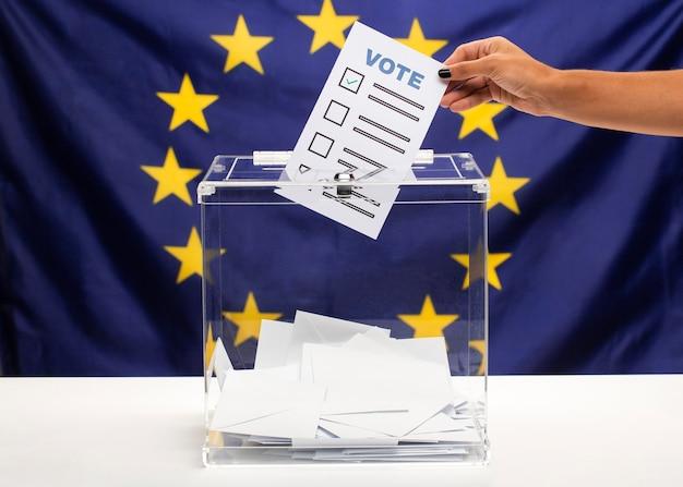 Boletín de votación sostenido a mano y puesto en la urna