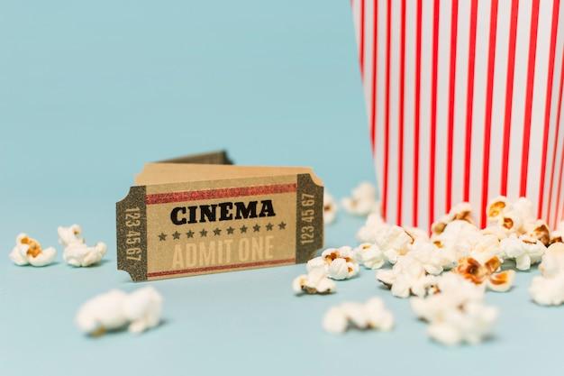 Boleto de cine cerca de las palomitas sobre fondo azul.